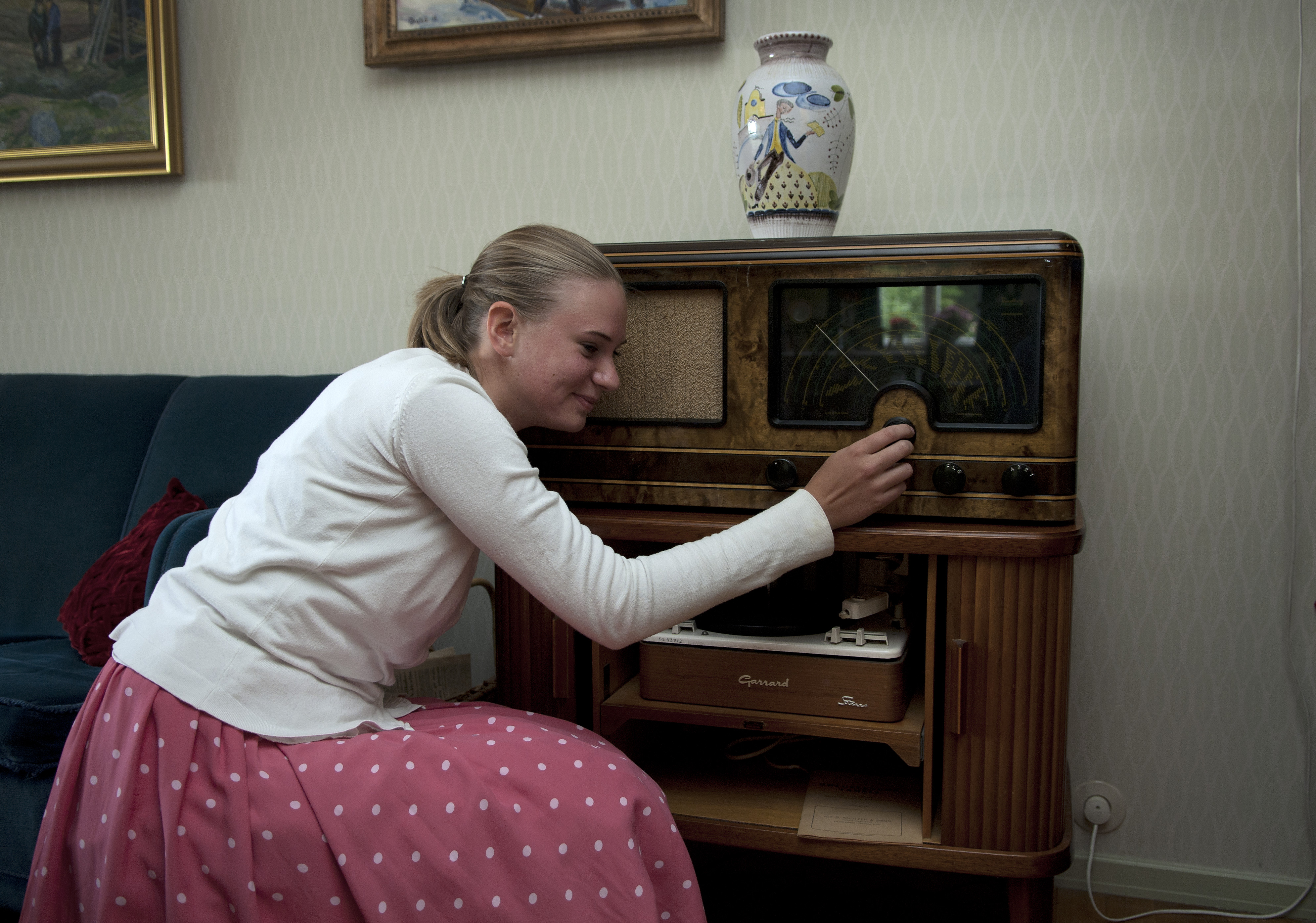 Jente i 1950-tallsklær lytter til en stor gammeldags radio.