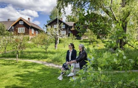 Gjester sitter på benk i hagen på Bjerkebæk
