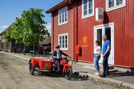 Gjester møter postmester utenfor Norges Postmuseum på Maihaugen